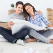 Portrait of man and woman holding house plans — Stock Photo