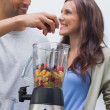 Stock Photo: Mputting fruits into blender