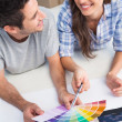 Happy couple looking at a color chart to decorate their house — Stock Photo