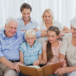 Extended family looking at an album photo — Foto de Stock