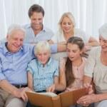 uitgebreide familie kijken naar een foto album — Stockfoto