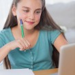 Smiling little girl doing her homework — Stock Photo