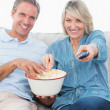 Couple watching tv and eating popcorn on the sofa — Stock Photo #28060955