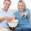 Couple watching tv and eating popcorn on the sofa — Stockfoto