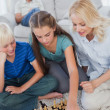 Siblings and mother playing chess sitting on a carpet — Stock Photo #28060971