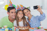 Woman taking pictures of her family during a birthday party — Stock Photo