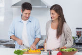 Man chopping mushrooms next to his pregnant partner — Stock Photo