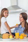 Cute girl giving an orange segment to her mother — Stock Photo