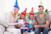Twins unwrapping birthday gift with their parents — Stock Photo