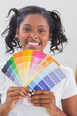 Smiling woman showing colour charts — Stock Photo