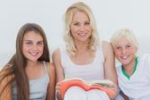 Portrait of mother holding a storybook to her children — Stock Photo