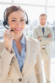 Smiling call centre agent with colleague behind her — Stock Photo