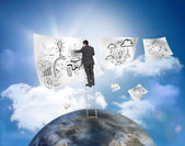 Businessman on a ladder over a planet drawing on a paper — Stock Photo