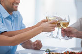 Close up of hands clinking glasses of white wine — Stock Photo