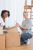 Cheerful friends unpacking boxes in new home — Stock Photo