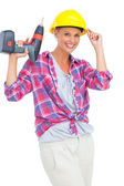 Smiling handy woman holding a power drill — Stok fotoğraf
