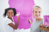 Cheerful young housemates painting wall pink — Stock Photo