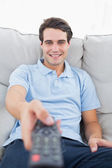 Portrait of a cheerful man changing channel — Stock Photo
