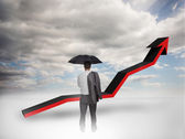 Businessman under an umbrella looking at a red arrow — Stock Photo