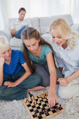 Siblings and mother playing chess sitting on a carpet — Stock Photo