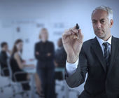 Businessman holding a marker and writing something — Stock Photo