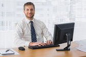 Businessman sitting at desk smiling — Stock Photo