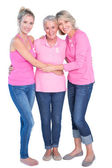 Cheerful women wearing pink tops and ribbons for breast cancer — Stock Photo