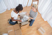 Young housemates unpacking in new home — Stock Photo