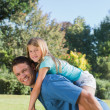 Stock Photo: Daughter getting piggy back from dad smiling at camera