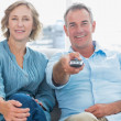 Cheerful middle aged couple sitting on the couch watching tv — Stock Photo #29444999