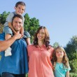 Happy family smiling at camera in the park — Stock Photo