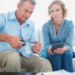Husband cutting credit card in half with wife looking at camera — Stock Photo #29445075