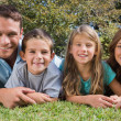 Smiling family lying on the grass — Stock Photo