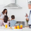 Father looking at his family cooking in the kitchen — Stock Photo
