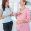Smiling pregnant woman holding cookies and her friend — Stock Photo