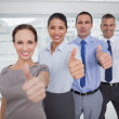 Smiling work team giving thumbs up — Stock Photo