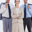 Stock Photo: Cheerful businesswomposing with her work team