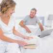 Smiling woman reading book while husband is using laptop — Stock Photo #29445427