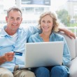 Happy couple sitting on their couch using the laptop to buy onli — Stock Photo