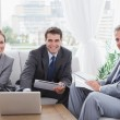 Business people smiling at camera while having a meeting — Stock Photo #29445449