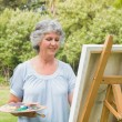 Cheerful mature woman painting on canvas — Stock Photo #29445461