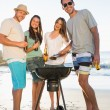 Stock Photo: Happy friends looking at camera while having barbecue together