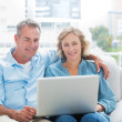 Smiling couple sitting on their couch using the laptop — Stock Photo #29445509