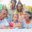 Cheerful extended family watching girl blowing out birthday cand — Stock Photo #29445511