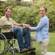 Handsome man in wheelchair with partner kneeling beside him — Stock Photo #29445525