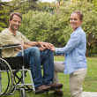 Handsome man in wheelchair with partner kneeling beside him — Stock Photo