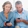 Smiling couple using their smartphones — Stock Photo