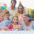 Happy extended family blowing out birthday candles together — Stock Photo #29445851