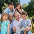 Multi generation family with a tablet pc sitting in park — Stock Photo #29445853