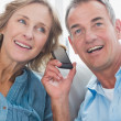 Smiling couple listening to mobile phone together — Stock Photo #29445965